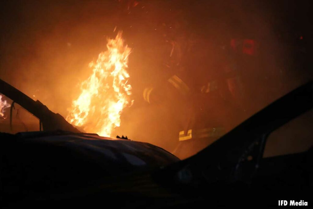 Firefighters with flames emerging from a vehicle in Indianapolis