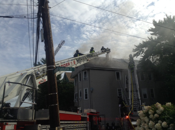 Boston firefighters work at a four-alarm fire. On Ladder 11's stick.