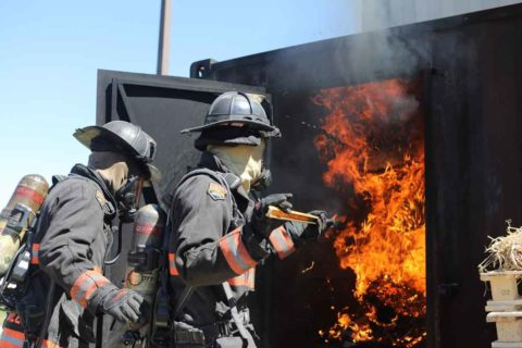 Firefighters stoking flames in the flashover can