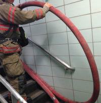 Firefighter moving a line up the stairs